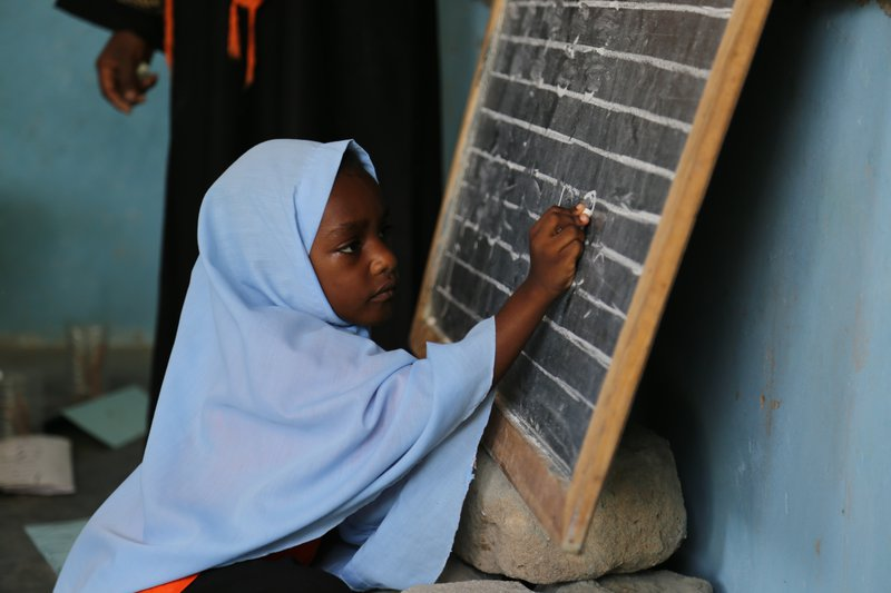(A little girl writes numbers from 1 to 5 on the blackboard at Mnyimbi TuTu Center in Zanzibar. Tanzania, April 2017 Photo Credit: GPE/Chantal Rigaud)